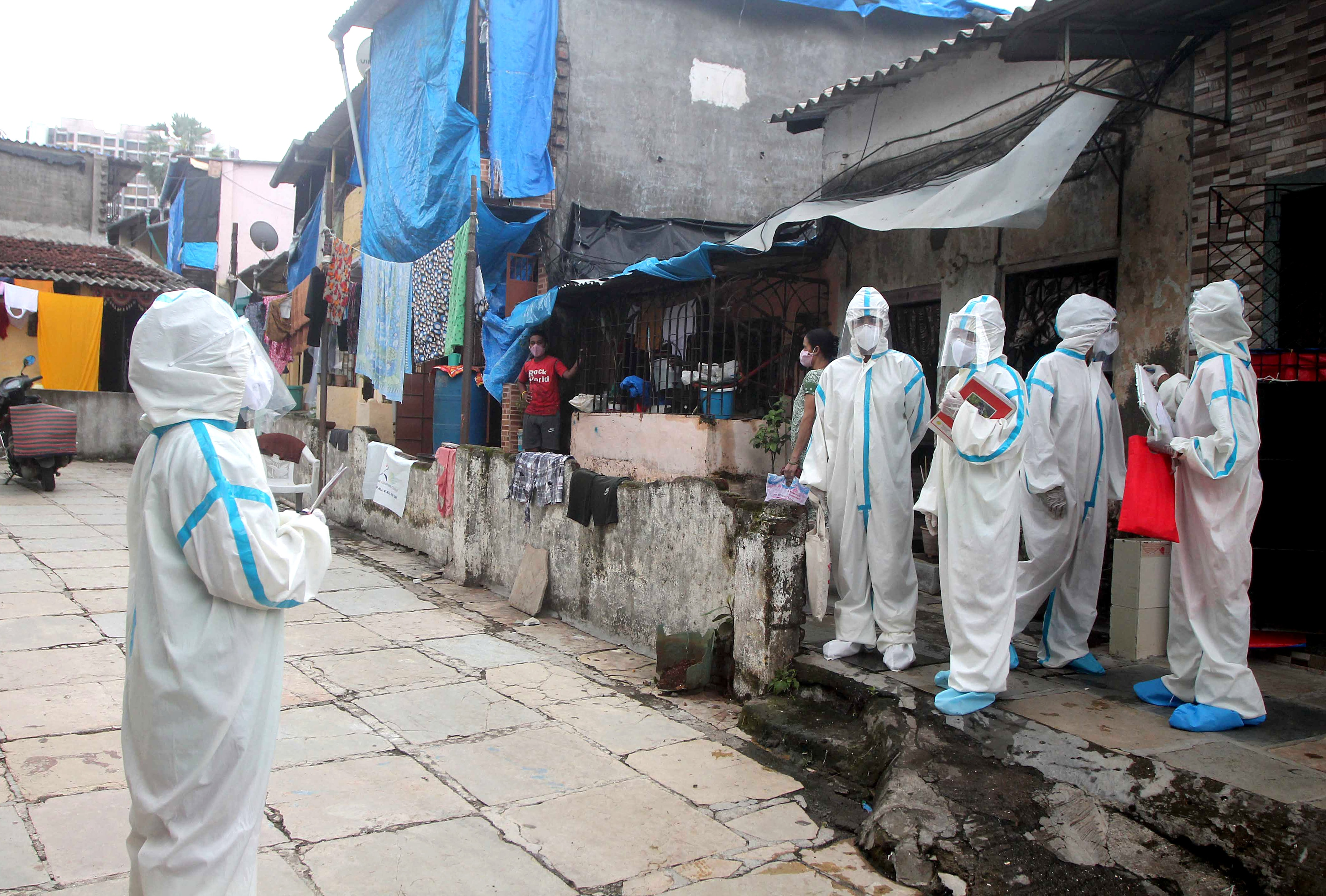 Health workers wear protective gear on the way to take health details of the residents of a 'containment zones' at the Kajupada area in Mumbai