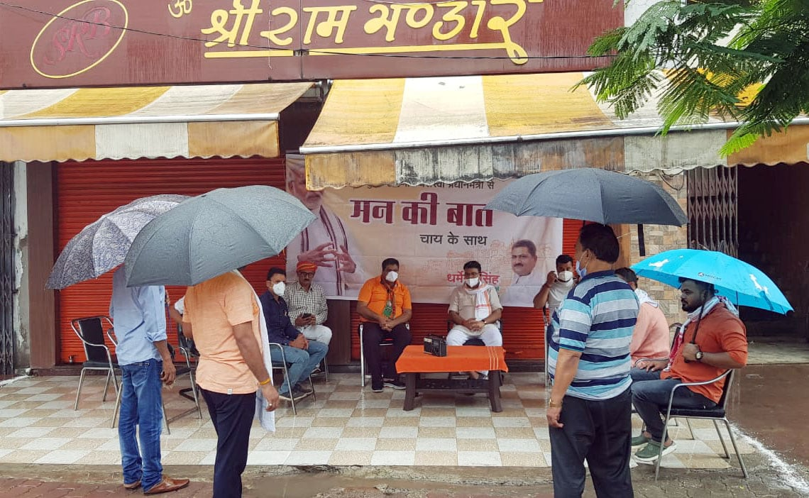 People hold umbrella listening 'Mann Ki Baat' programme through radio during rain in Varanasi