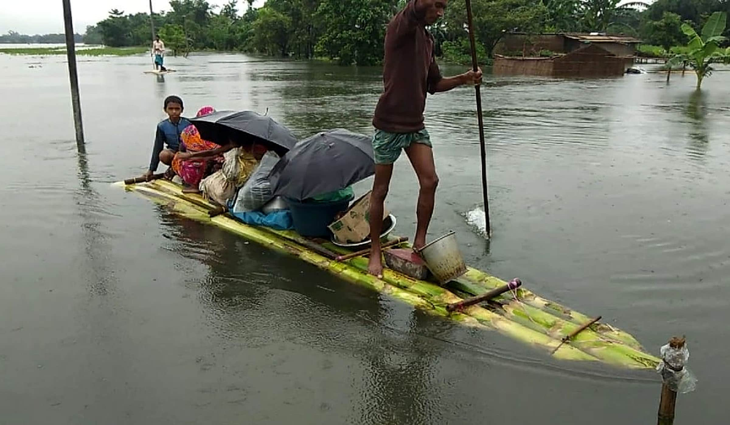 Villagers carrying their belongings move to a safer place through a makeshift boat, after their houses submerged in water due to heavy rainfall, in Bongaigaon on Saturday