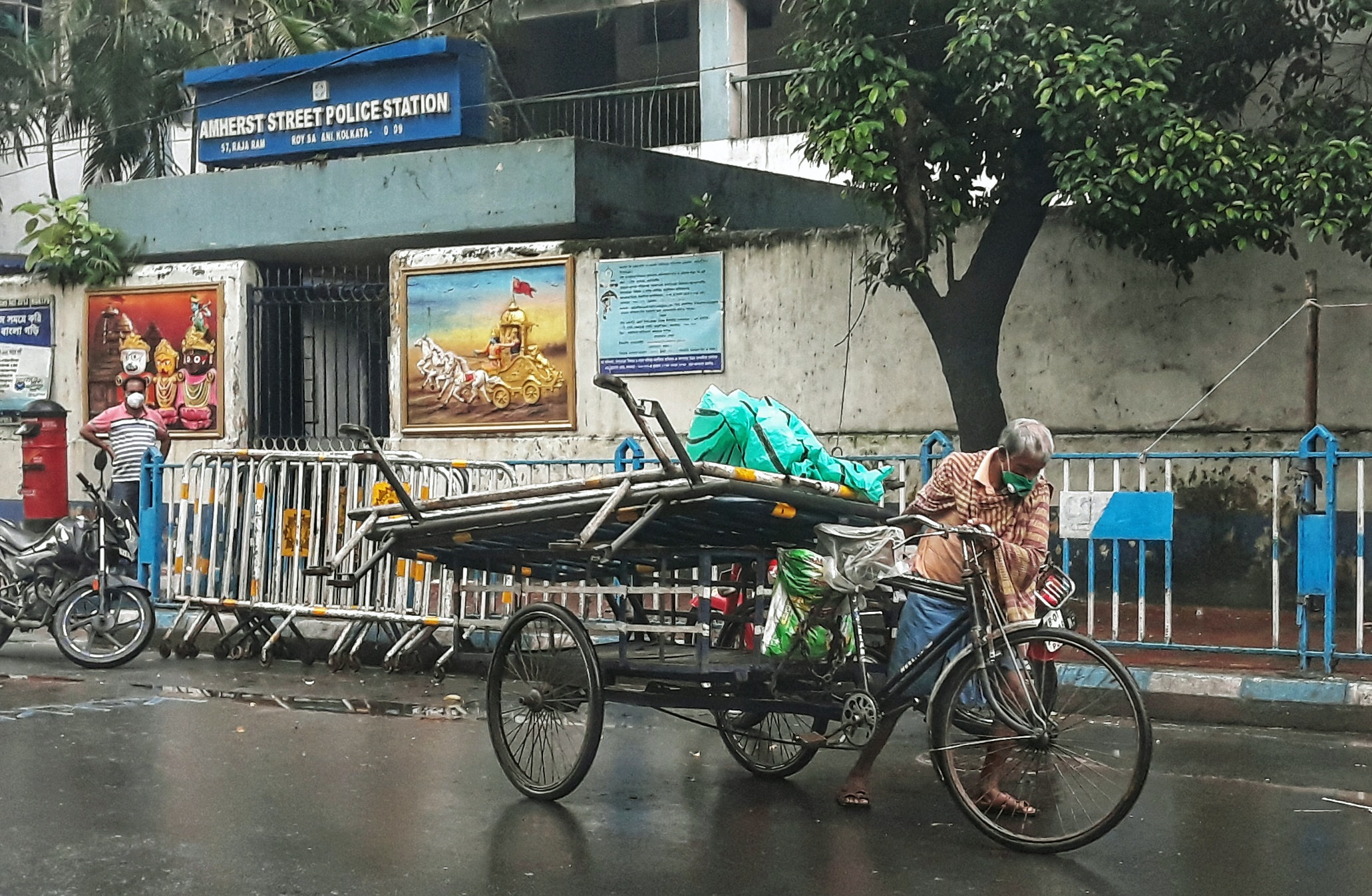 A rickshaw puller carries barricade in his cart during a rainfall, in Kolkata on Thursday. Photo: ANI