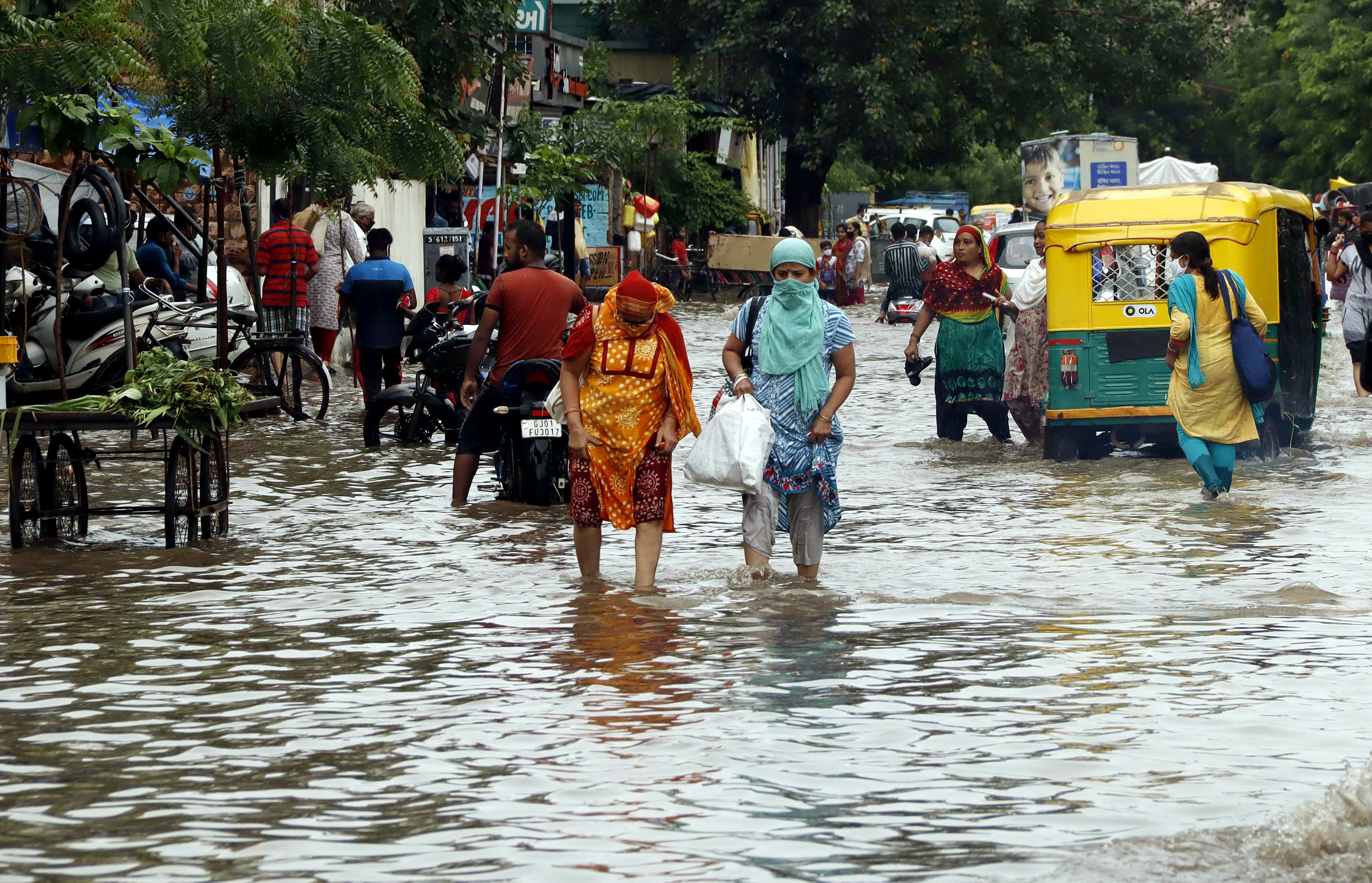 People wade through a flooded street after heavy rain in Ahmedabad on Friday.