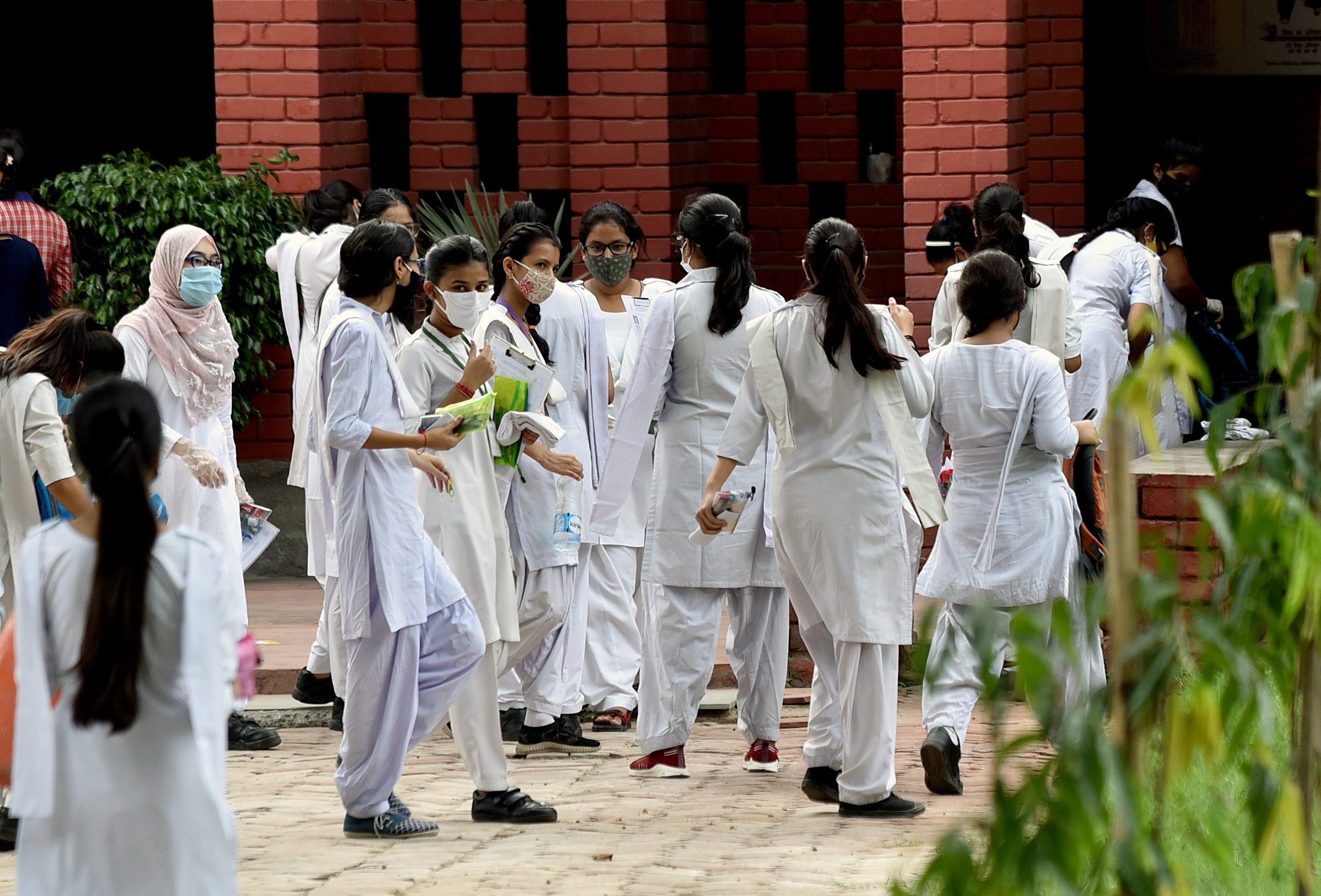 Students of class 10th wearing masks arrive to appear for compartment exam at an examination centre amid Coronavirus disease, in New Delhi on Wednesday.