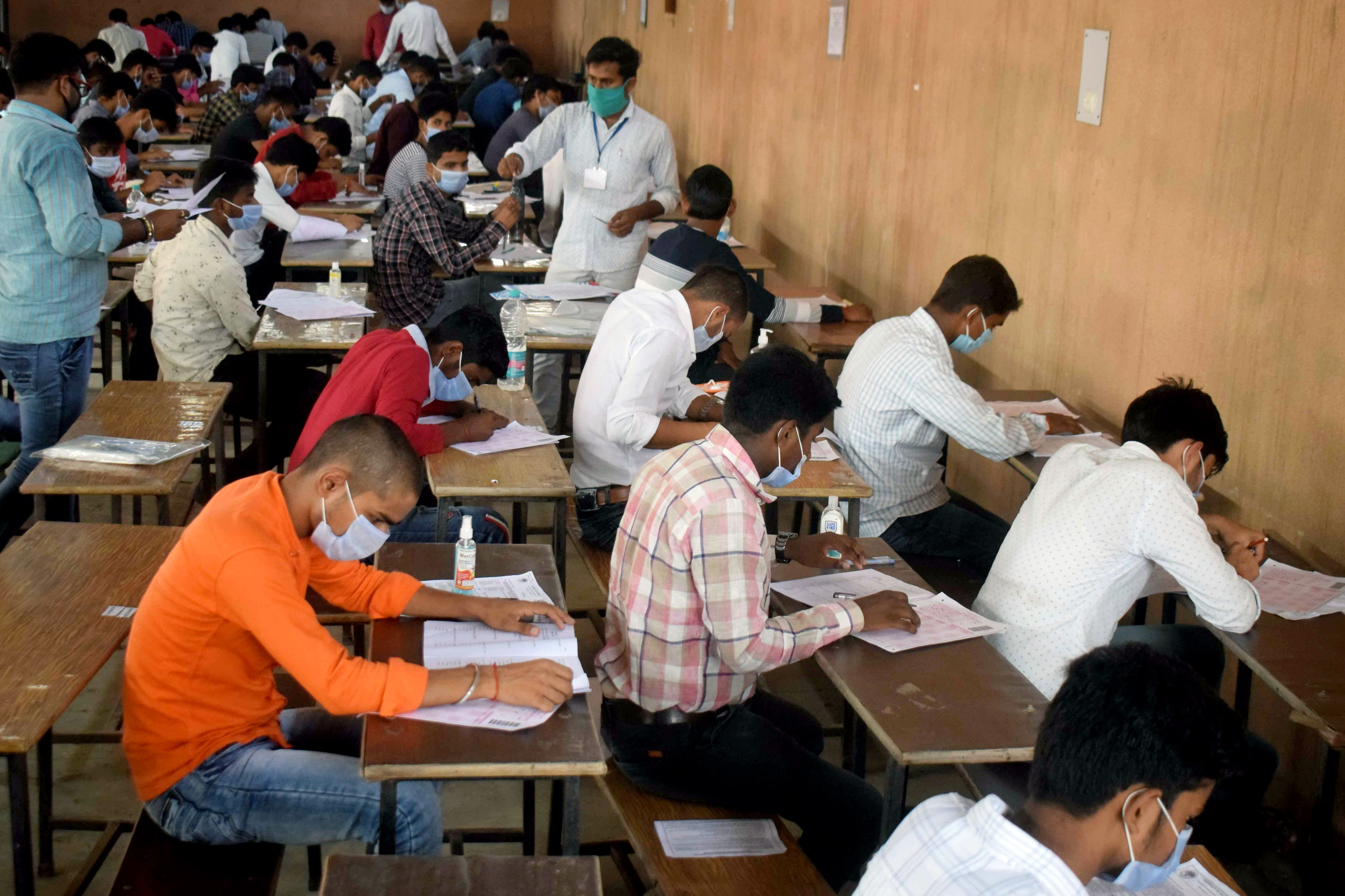 Applicants appear in the Allahabad Central University (UGAT) entrance exam at an examination center, in Prayagraj on Saturday.