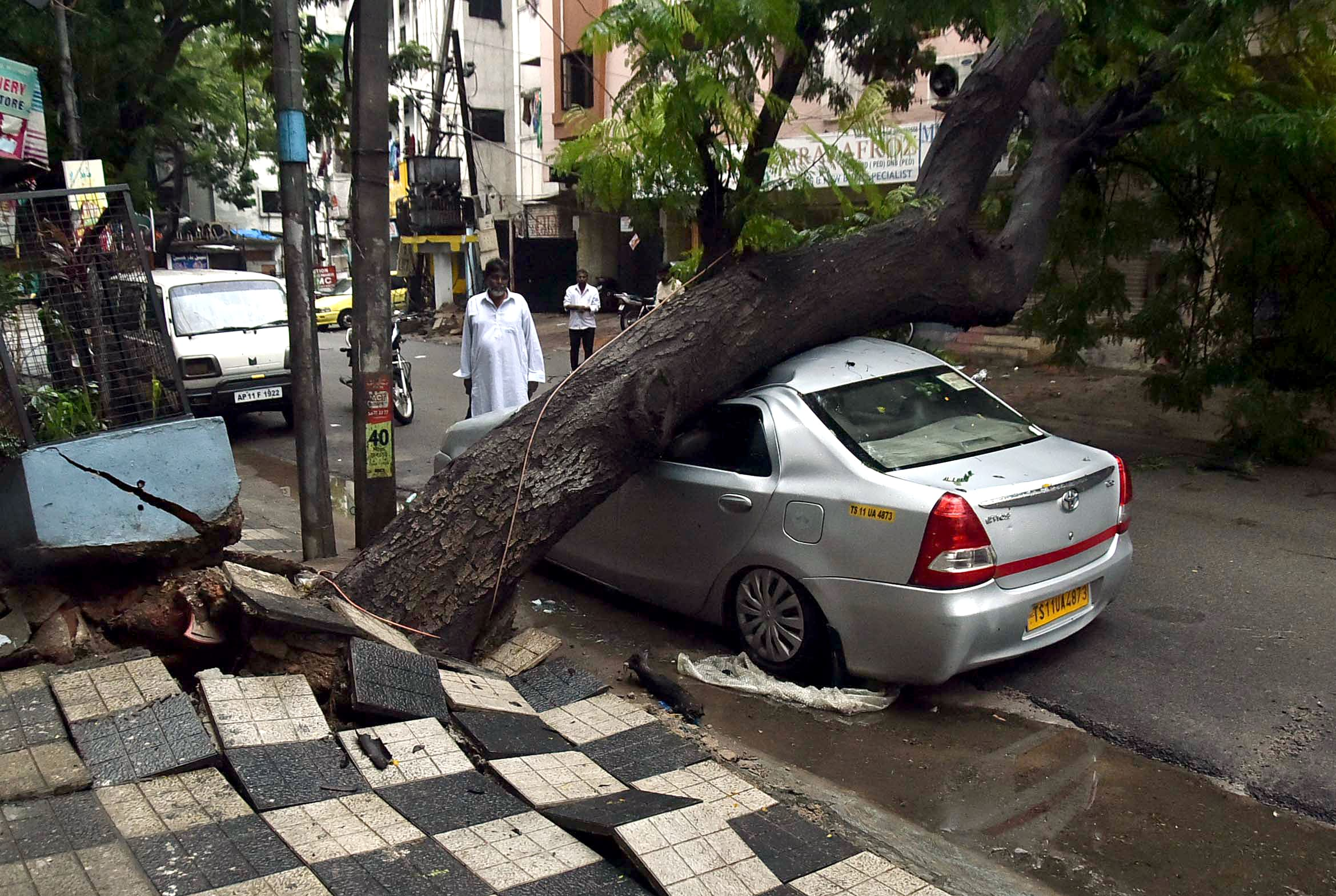 A tree fell down on a car at Noor khan Bazar after heavy rain in Hyderabad on