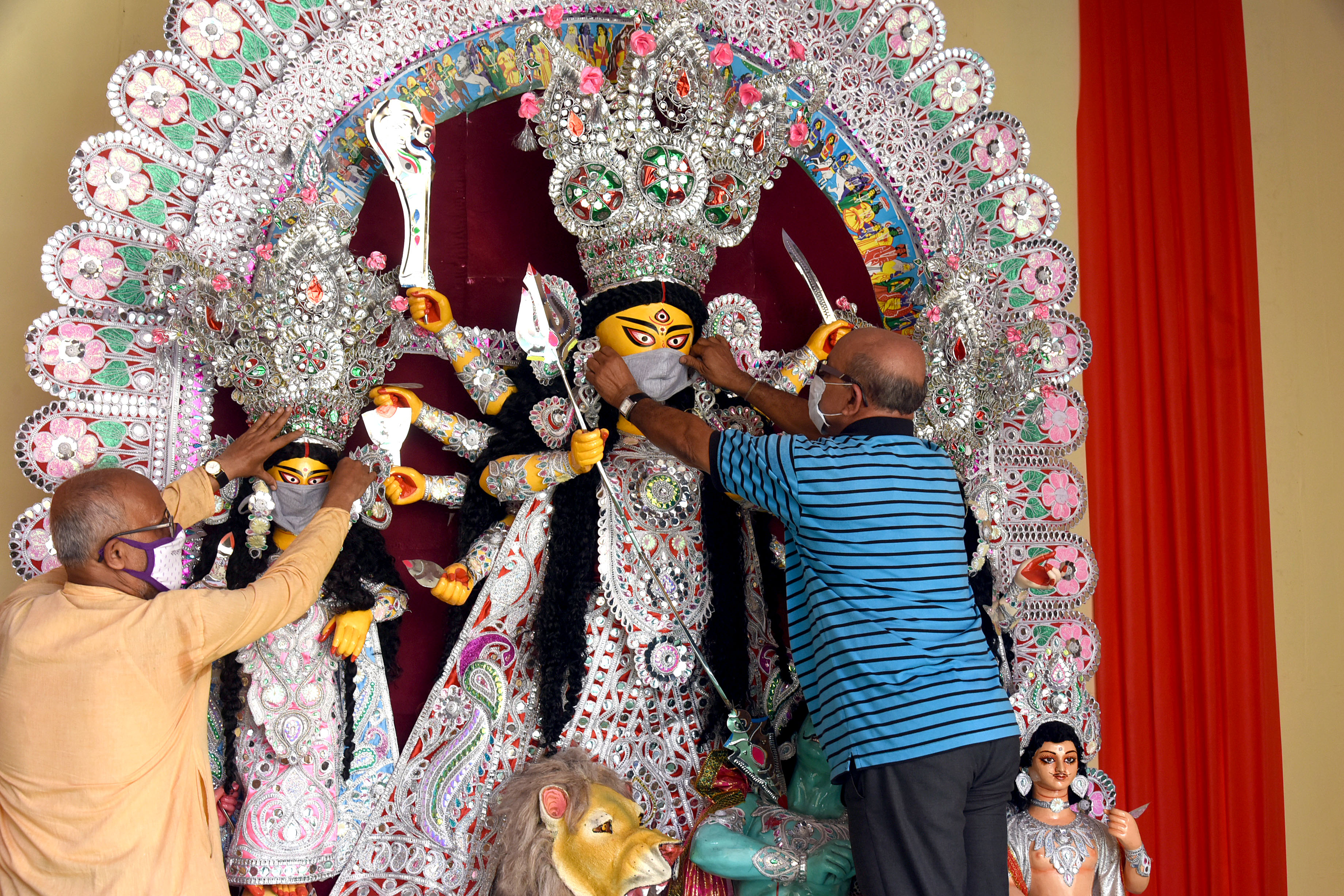 A man covering the face of Goddess Durga's idol with a face-mask to create awareness regarding covid-19 during the Durga Puja festival, in Kolkata on Tuesday.