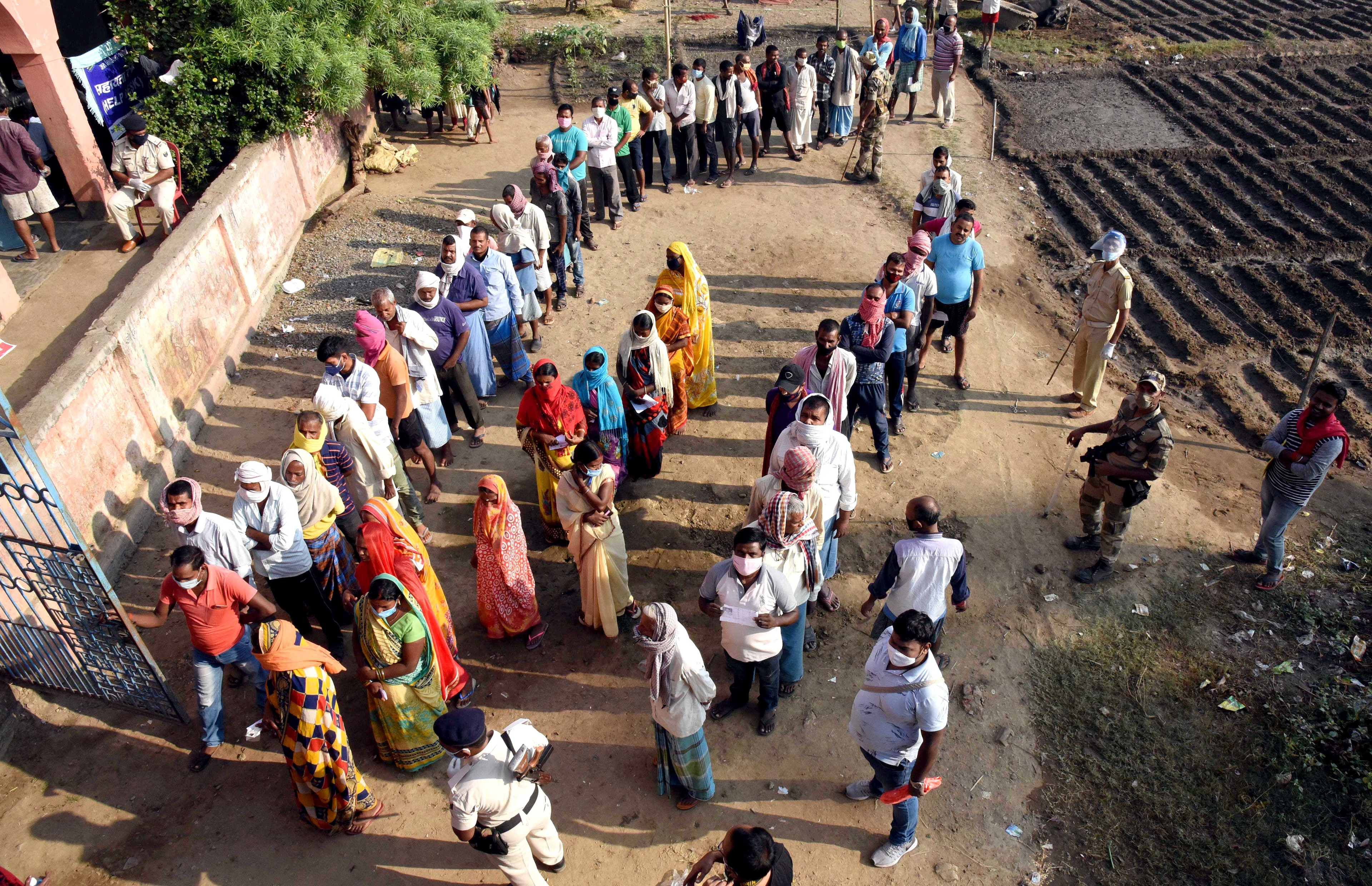 Security personnel stand guard as voters stand in queues at the polling station to cast their votes in the first phase of Bihar Assembly polls at  Masaudhi, in Patna on Wednesday.