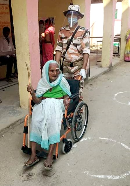 ITBP personnel helps an specially abled woman as she arrives to cast her vote for the first phase of Bihar Assembly polls, in Nawada District on Wednesday.