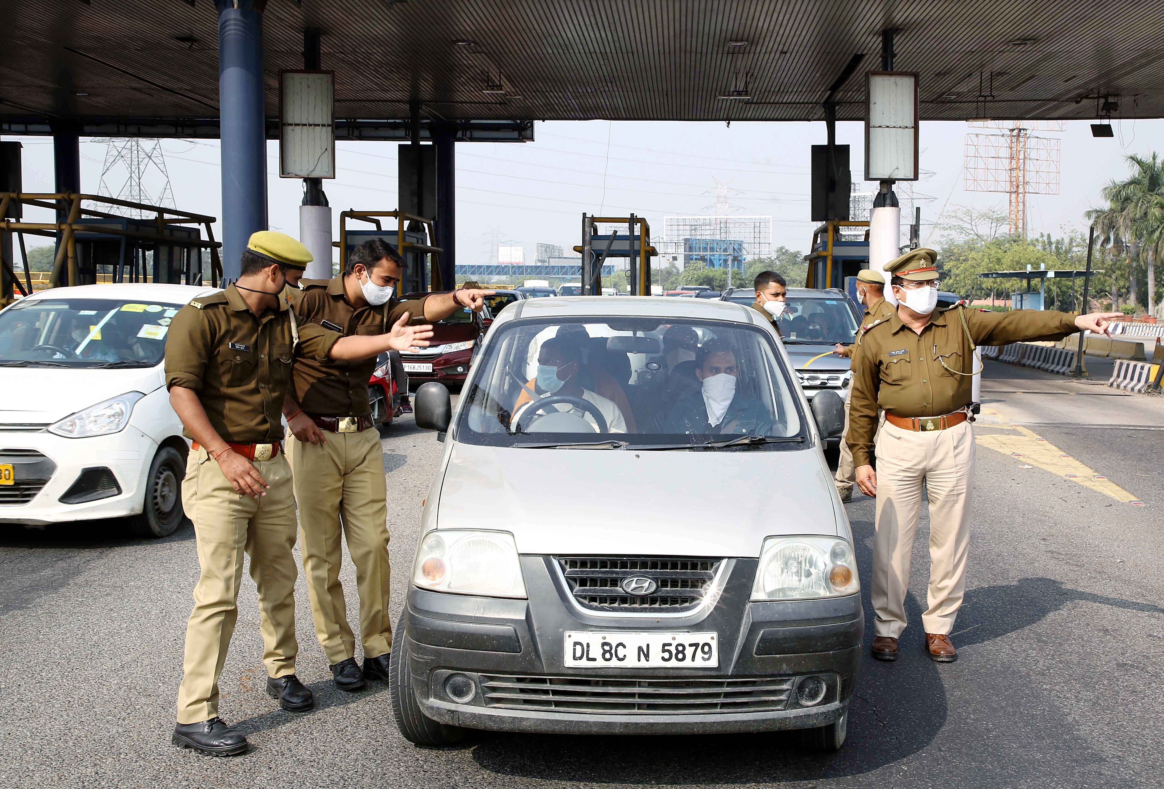 Police personnel stop people for random testing at the Delhi Noida border on Wednesday