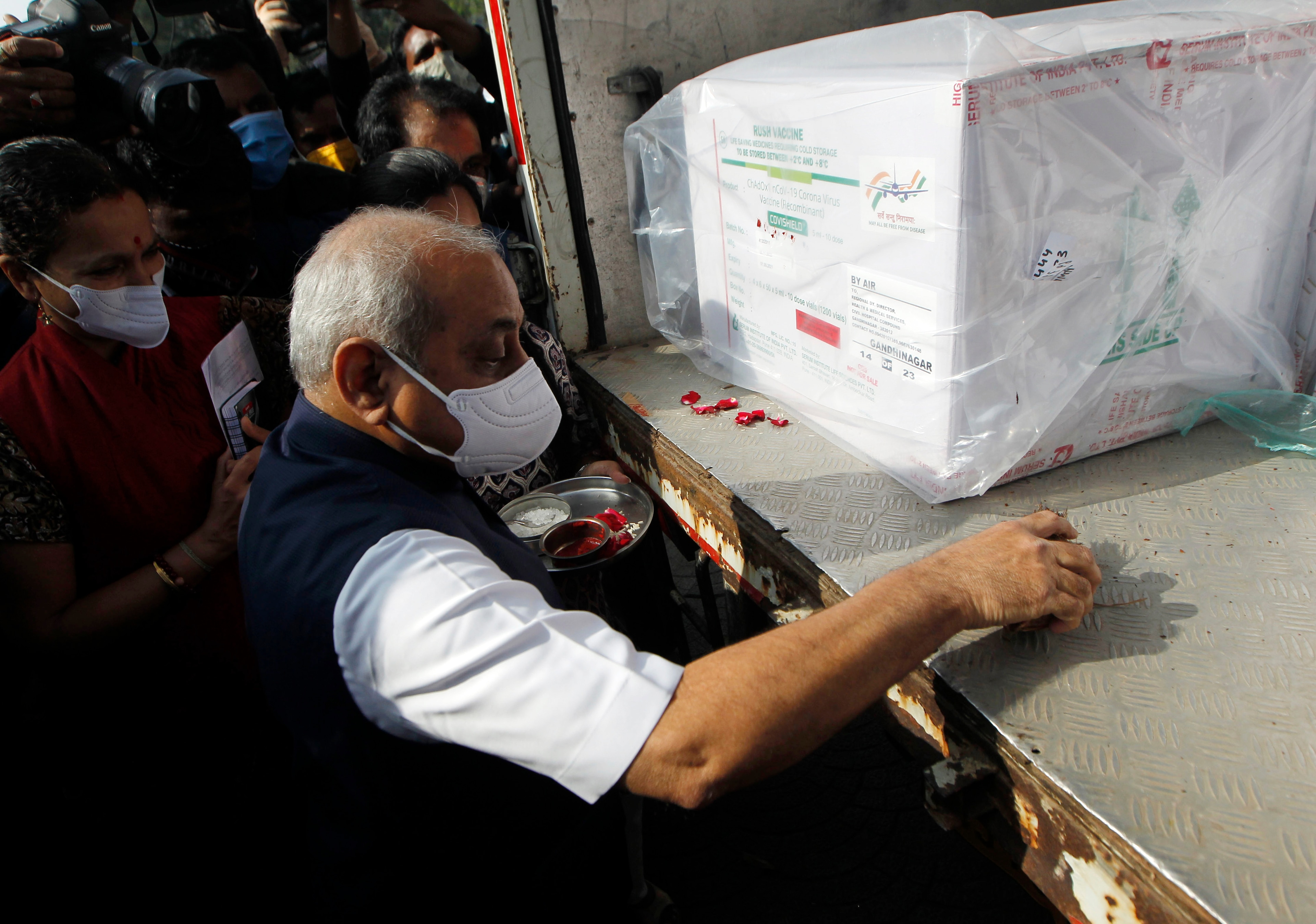 Deputy Chief Minister Nitin Patel offering prayer in front of the COVISHIELD vaccine consignment from Serum Institute of India as it arrives at the Ahmedabad airport, ahead of the rollout of the vaccination program, in Ahmedabad on Tuesday.