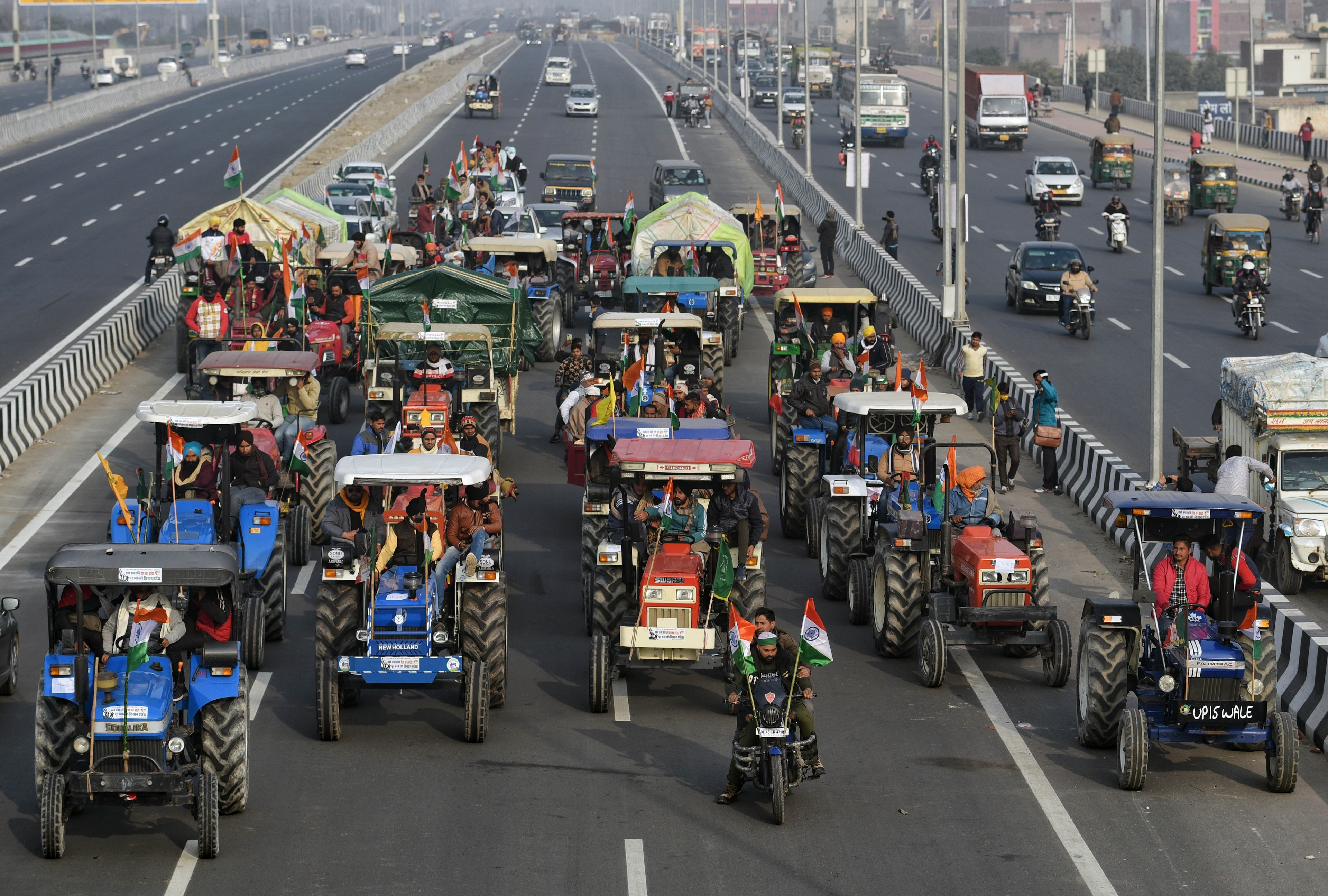 Farmers ride a tractors during their protest against farm laws at Ghazipur border  in New Delhi