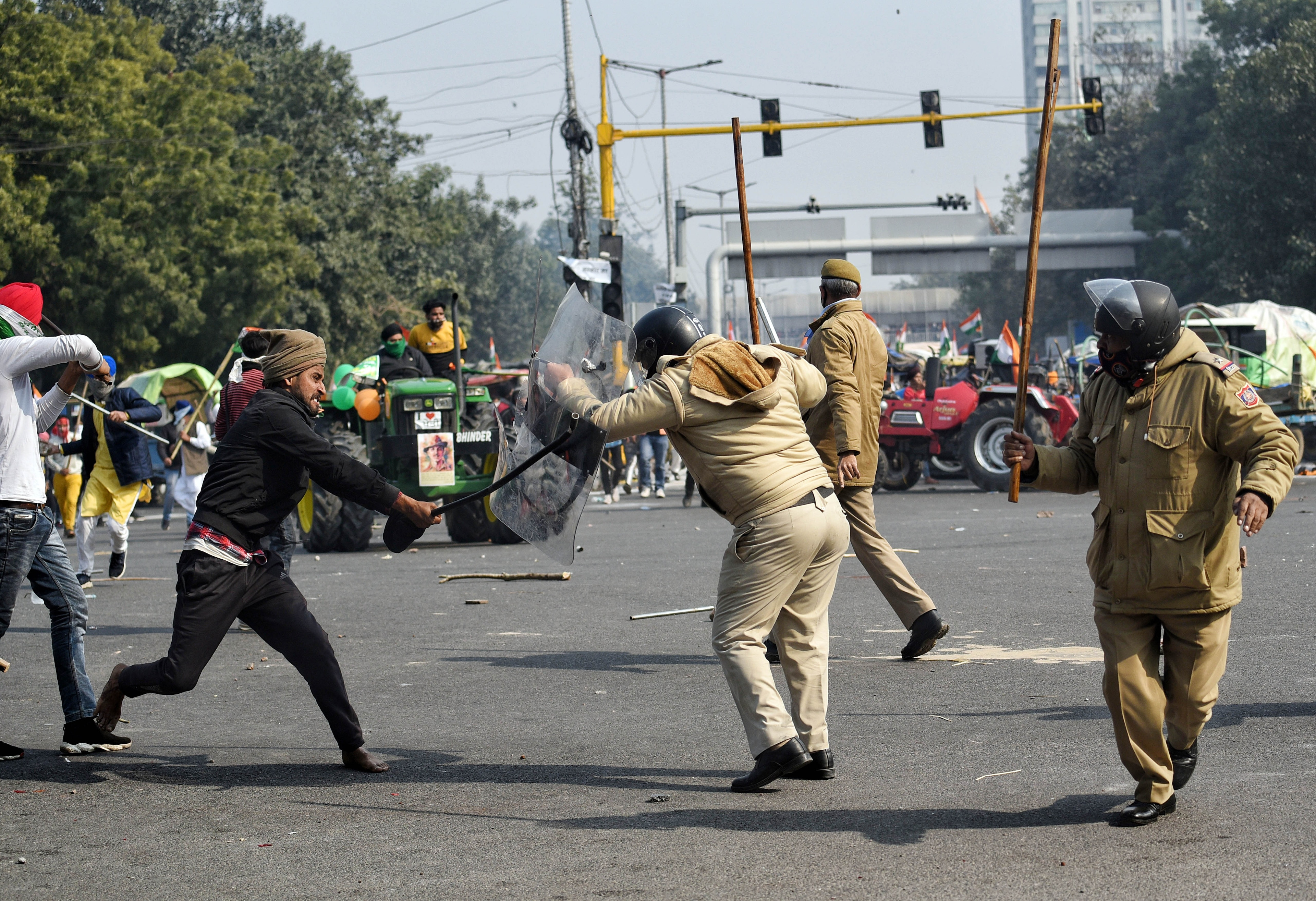 A Protester hits police personnel with a rod after breaching the route during the tractor rally at ITO in New Delhi