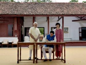 Prime Minister Narendra Modi looks on as Japanese Prime Minister Shinzo Abe signs the Visitor's Book at Gandhi Ashram in Ahmedabad on Wednesday. Abe's wife Akie is also seen