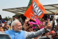 PM-elect Narendra Modi waves victory sign on his arrival at the IGI Airport in New Delhi