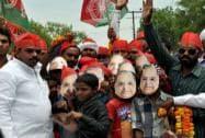 Supporters wear masks of Mulayam Singh Yadav