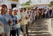 Voters wait in a long queue to cast their votes