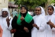 A Muslim woman along with Christian nuns showing inked fingers