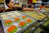 A man displays sweets with Narendra Modi's image at a sweet shop in Kolkata