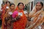 Voters show their voter ID cards outside a polling booth during repolling in West Bengal