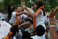 Arvind Kejriwal shakes hands with a small girl at an election road show in Varanasi