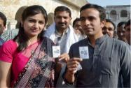 Jayant Chaudhary and his wife Charu show their voter identity card before casting votes