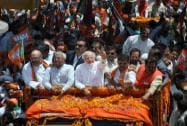 Narendra Modi waves at supporters during a road show before filing his nomination papers in Varanasi