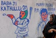 A woman looks at a wall grafiti of different political parties