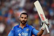 Indian batsman Shikhar Dhawan raises his bat as he celebrates his century