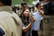 An irate guardian talks to the police officers during a protest at a school where a 6-year-girl was raped