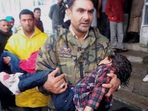 A policeman carries an injured child to a hospital