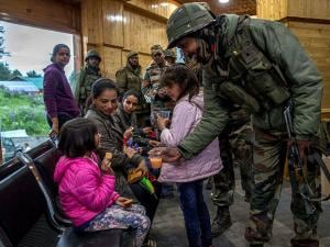 An army soldier offers juice to children after a rescue mission in Gulmarg