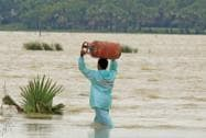 man wades through floodwaters carrying a gas cylinder