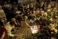People hold candles and place flower tributes placed outside the Dutch embassy to commemorate victims of Malaysia Airlines plane crash in Kiev