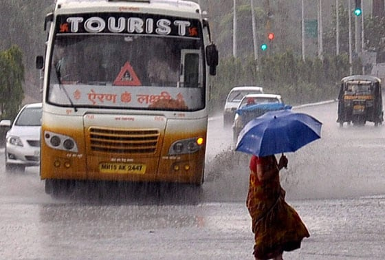 A woman walks through pre-monsoon showers which brought some respite from the heat to the people, in Jaipur on Monday