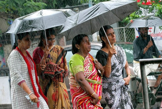People walk with umbrella during heavy rain in Kozhikode on Saturday
