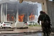 Afghan security forces watch a house burn