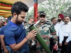 Rohit Sharma trying to know about the functioning of a mortar shell launcher as they spend time with the soldiers of 124 Sikh Battalion