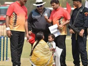 UP CM Akhilesh Yadav talks to a woman who barged inside the ground while he was taking part in a cricket match between CM Eleven and IAS Eleven in Lucknow