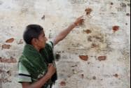 A boy shows bullet marks on the wall of his house allegedly fired from Pakistan's side in Gharna village
