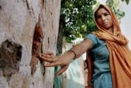 A villager shows bullet marks on the wall of her house allegedly fired from Pakistan's side in Gharna village