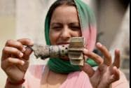 A woman shows a mortar shell recovered from a residential area