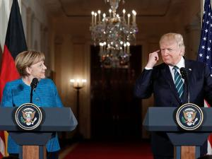 President Donald Trump points to his ear piece as he waits to listen for the translation while participating in a joint news conference with German Chancellor Angela Merkel