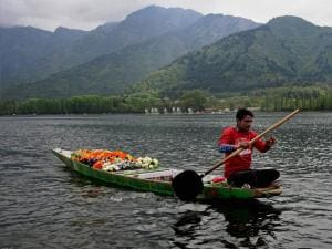 A flower vendor rows his boat during two day tourism festival at Dal Lake in Srinagar