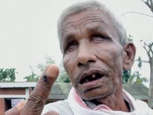A visually challenged voter shows his ink marked finger after casting the vote for the 1st phase of Assam state assembly elections in Jorhat