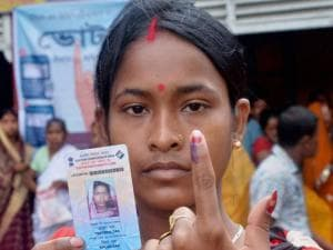 A woman voter shows her inked finger after casting vote at a polling booth for the first phase of the Assam assembly polls in Silchar