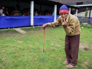 An elderly man shows his ink marked finger after casting the vote during the 1st phase of Assam state assembly elections in Jorhat
