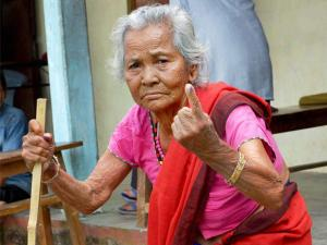 An elderly woman shows her ink marked finger after casting vote during the 1st phase of Assam state assembly elections in Bahguri