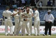 Australia's bowler Nathan Lyon, without cap, is congratulated by teammates