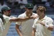 Australia's Shane Watson and Mitchell Starc talk after taking the wicket of West Indies' Jason Holder