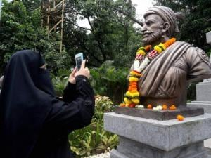A women capturing a picture of Shivaji's statue