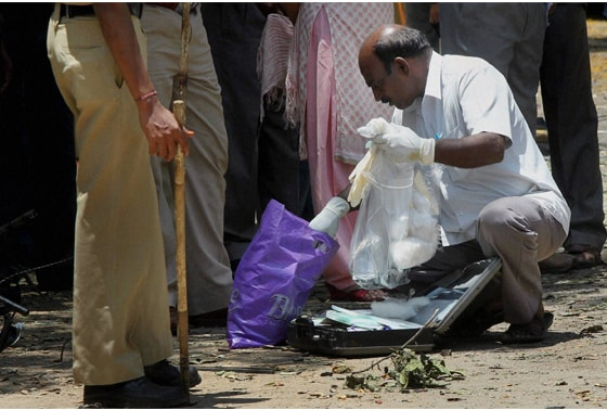 An expert collecting samples at the site of the blast near the BJP office at Malleswaram in Bengaluru
